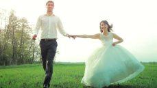 bride and groom running through field