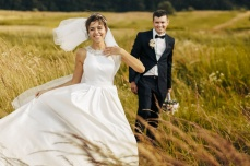 happy husband and wife walking together in field